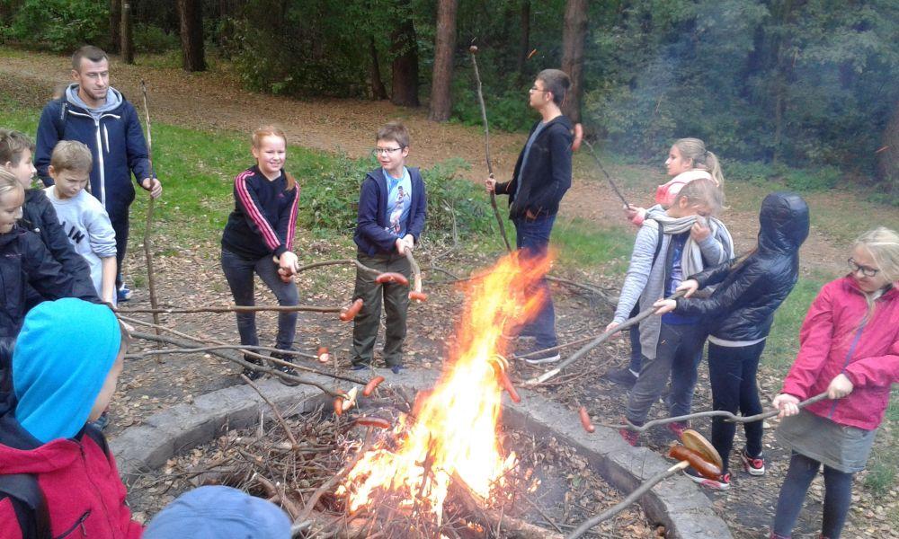 dzieci stoją w kręgu przy ognisku i pieką kiełbaski i chleb na patykach