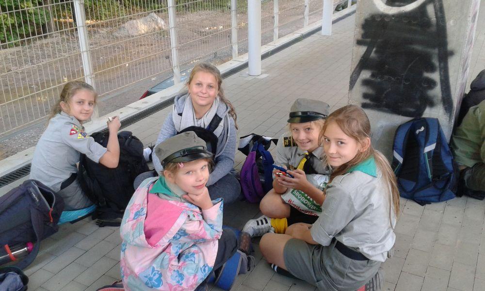 Harcerki siedzą na kręgu na peronie czekając na pociąg do Warszawy