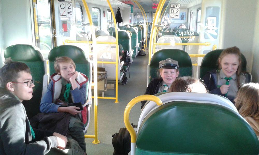 Harcerze siedzą w pociągu śmieją się i wspólnie rozmawiają w drodze na startówkę