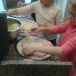 Dzieci na spodach pizzy posmarowanych sosem i posypanych serem układają wybrane przez siebie składniki pizzy – szynkę, salami