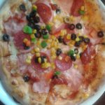 Zdjęcia pizzy wykonanej przez ucznia podczas warsztatów. Pizza z salami, szynką, czarnymi oliwkami, kukurydzą, czerwoną i zieloną papryką