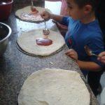 Dzieci na cieście pizzy rozsmarowują łyżkami sos pomidorowy