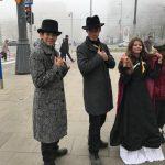 """uczestnicy jednego z punktów pt. """"Pokaz mody"""" pozują do zdjęcia przebrani w płaszcze, meloniki oraz sukienkę z dawnych czasów"""