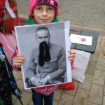 Dziewczynka trzyma czarno-biały portret Józefa Piłsudskiego z doklejonymi z czarnej włóczki wąsami