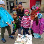 uśmiechnięte dzieci prezentują swoje dzieło –makietę grodu w Biskupinie wykonaną na kawałku styropianu z plasteliny i zapałek