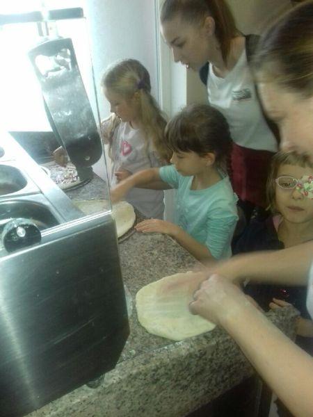 Dziewczynki nakładają na ciasto do pizzy wybrane przez siebie składnikii