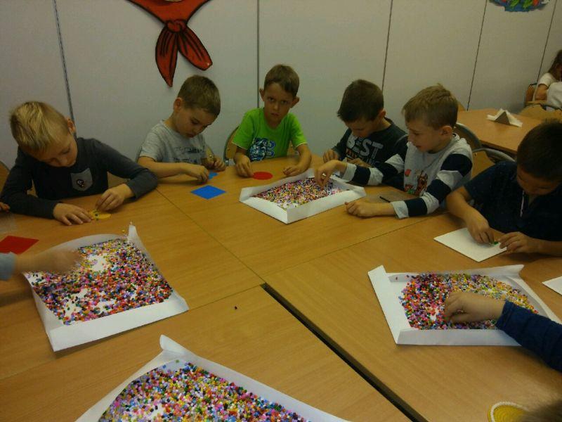 Dzieci układają koraliki.