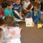 Dzieci przeglądają otrzymane pamiątkowe dyplomy i książki