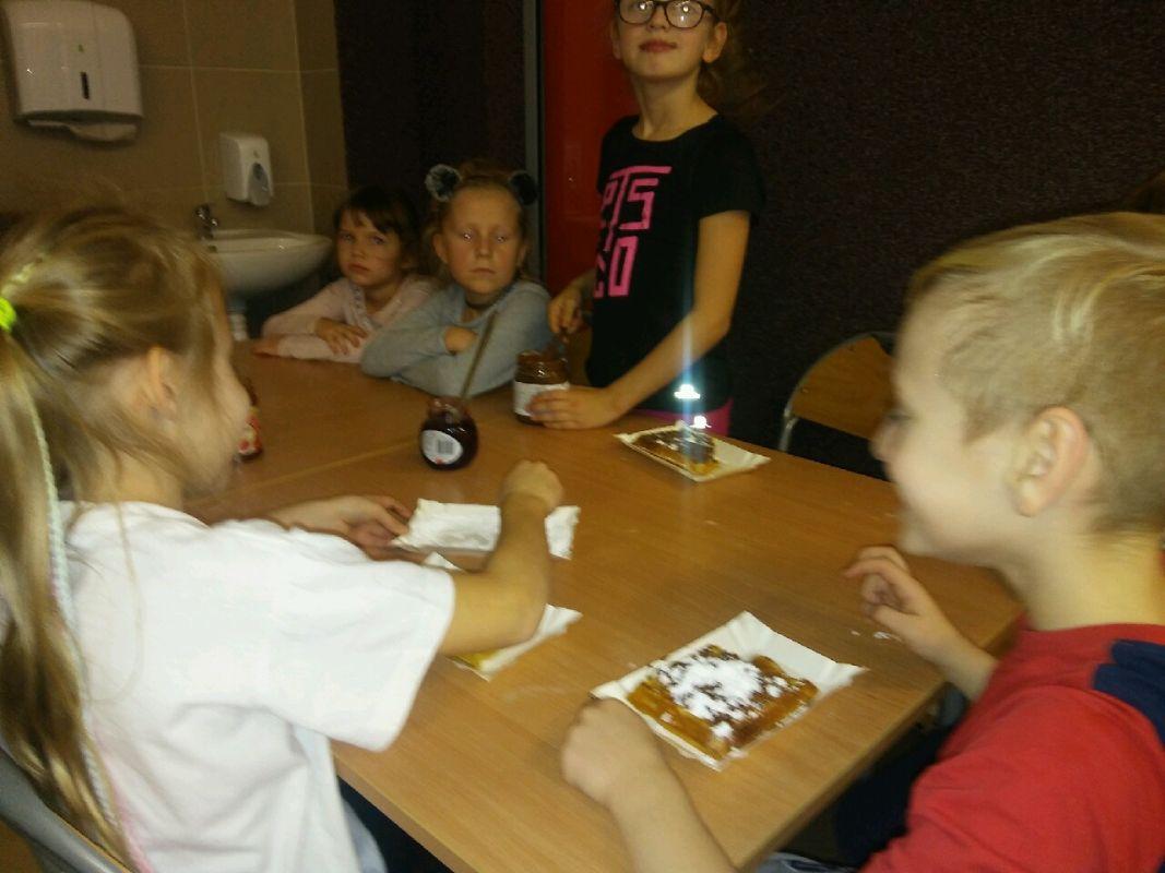 Dzieci jedzą przygotowane przez siebie gofry