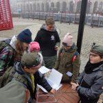 harcerze stojąc w grupie przeglądają zapisane kartki z zadaniem oraz tworzą budowle ze słomek