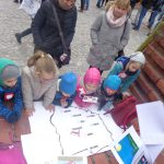 dzieci i rodzice stoją przed czarno-białą mapa polski na której zaznaczone są niektóre z polskich miast