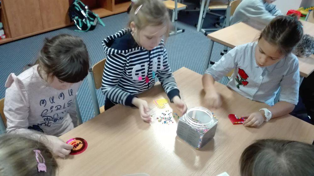 Dzieci układały z koralików różne rzeczy np. emotki, serduszka, naszyjniki itp.