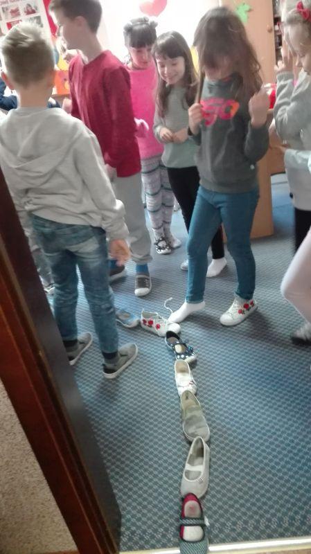 Chłopcy uczestniczą we wróżbie z butami