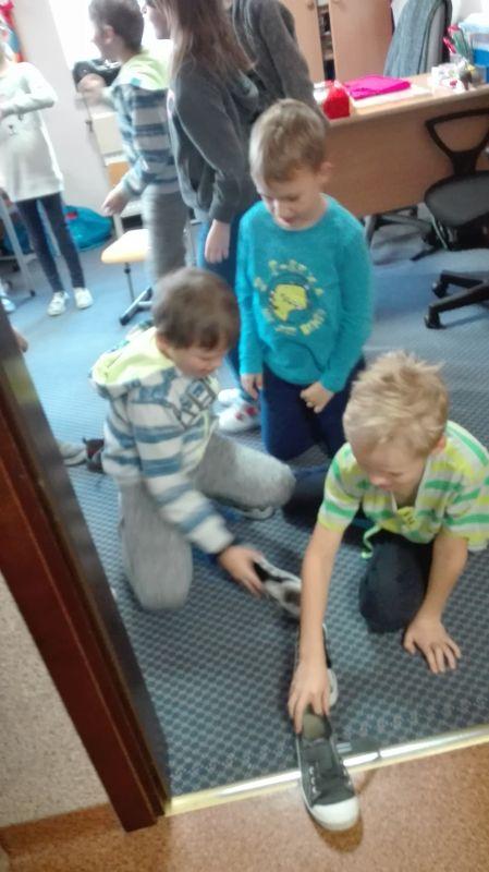 Dziewczynki uczestniczą we wróżbie z butami
