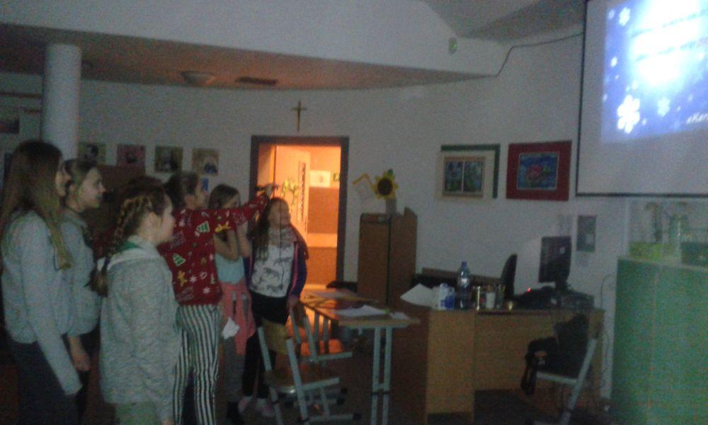 """ciemna sala z zapalonym projektorem na którym wyświetlają się słowa piosenki i grupa śpiewających dziewczyn z mikrofonem. Jeden z punktów na świątecznej grze harcerskiej """"zimowe karaoke"""""""