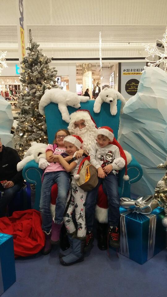 Trójka dzieci siedząca na kolanach Świętego Mikołaja, obok duże paczki prezentów, nad nimi zawieszone na imitacji góry lodowej misie polarne – maskotki