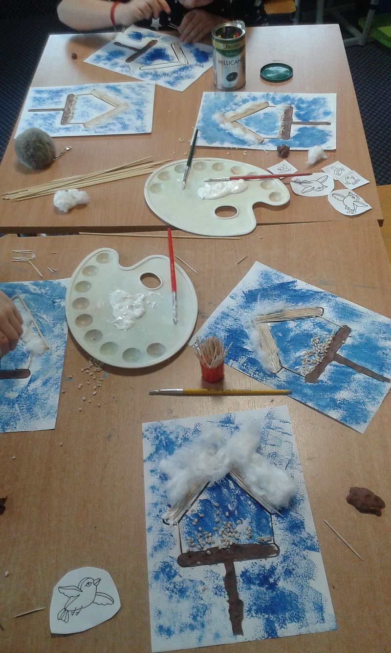 na ławkach są porozkładane prace dzieci, które dalej kończą. Na pracach na niebieskim tle są karmniki wykonane z wykałaczek, plasteliny, waty oraz kaszy