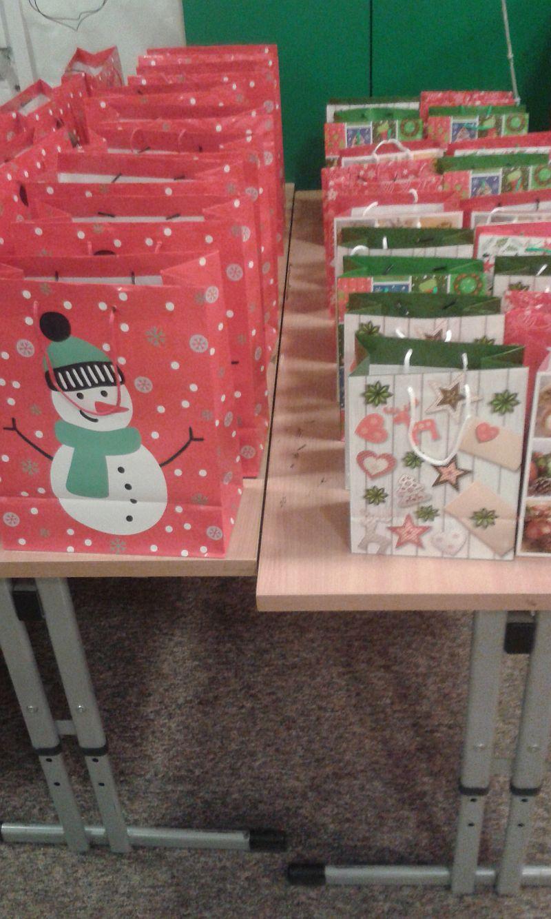 stolik na którym ustawione są w rzędach świąteczne torebki z prezentami dla zuchów i harcerzy