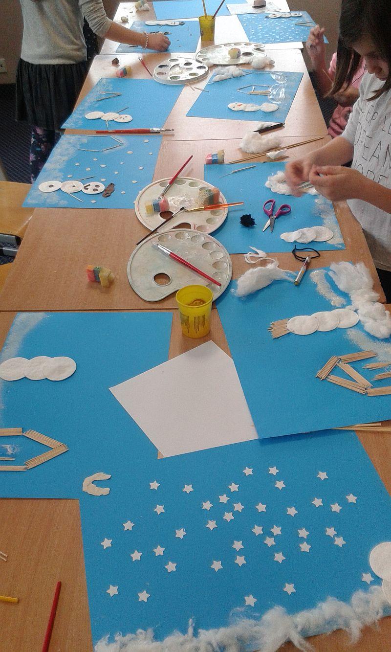 na ławkach są porozkładane prace które robią dzieci. Na niebieskim tle są wykonane z pomocą m.in. waty, wykałaczek i farb zimowe krajobrazy, bałwany