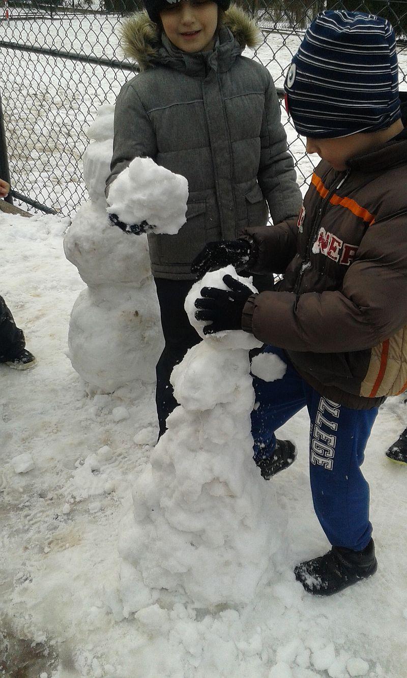 Chłopiec buduje ze śniegu bałwana, drugi stojący obok podaje mu kule ulepioną ze śniegu
