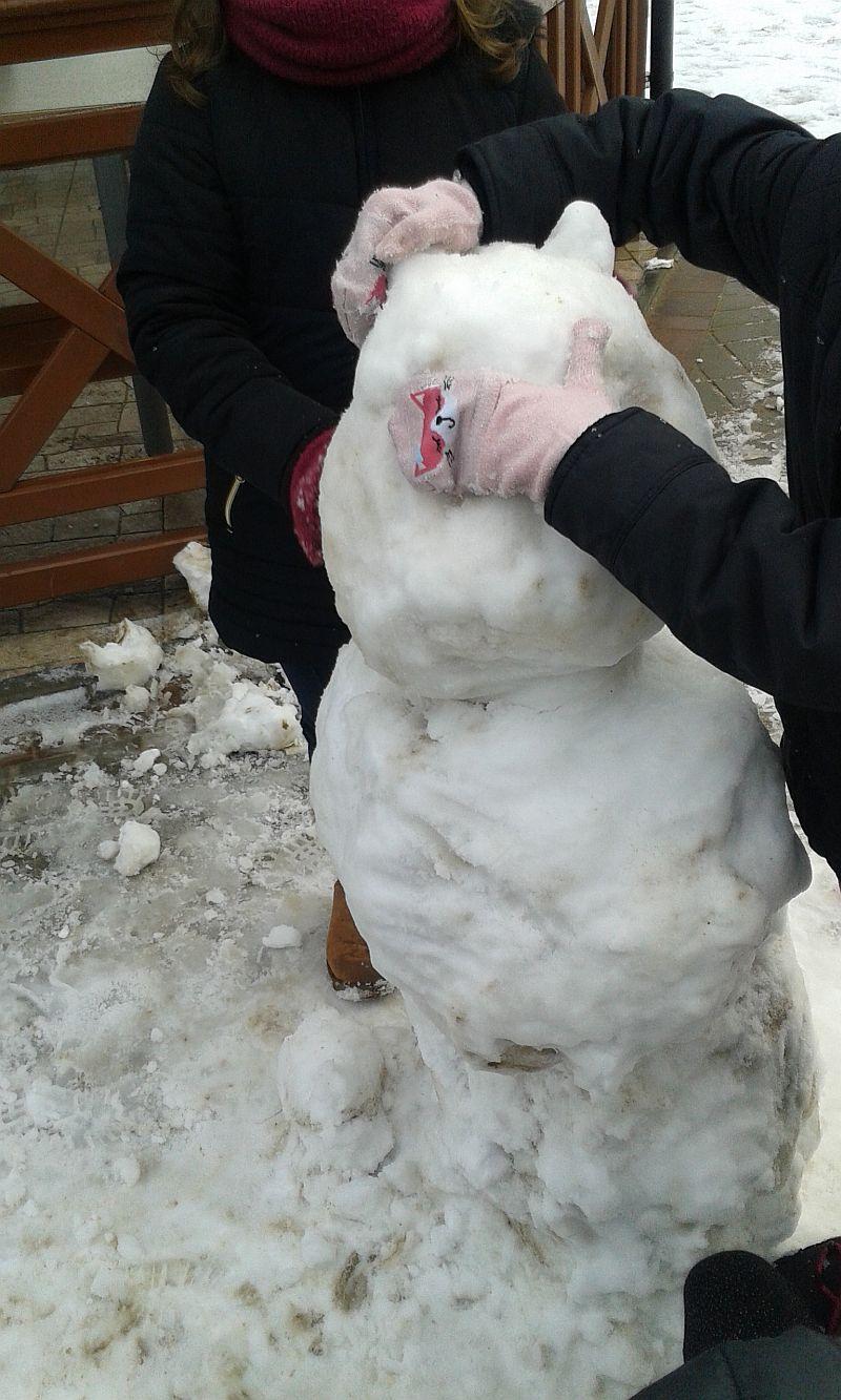 dzieci budują ze śniegu misia, dziewczynka ręką w rękawiczce formuje śnieżnemu misiowi oko