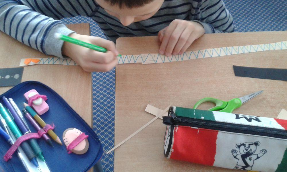 uczeń mazakiem ozdabia swój indiański pióropusz rysując na nim zielone kreski-trójkąty