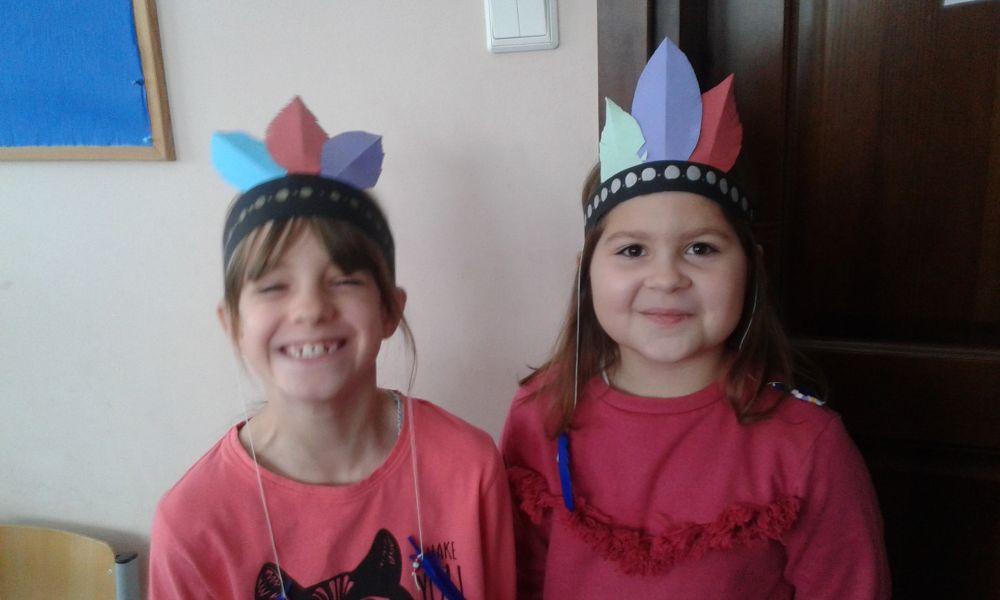 2 uśmiechnięte uczennice w wykonanych własnoręcznie pióropuszach na głowach