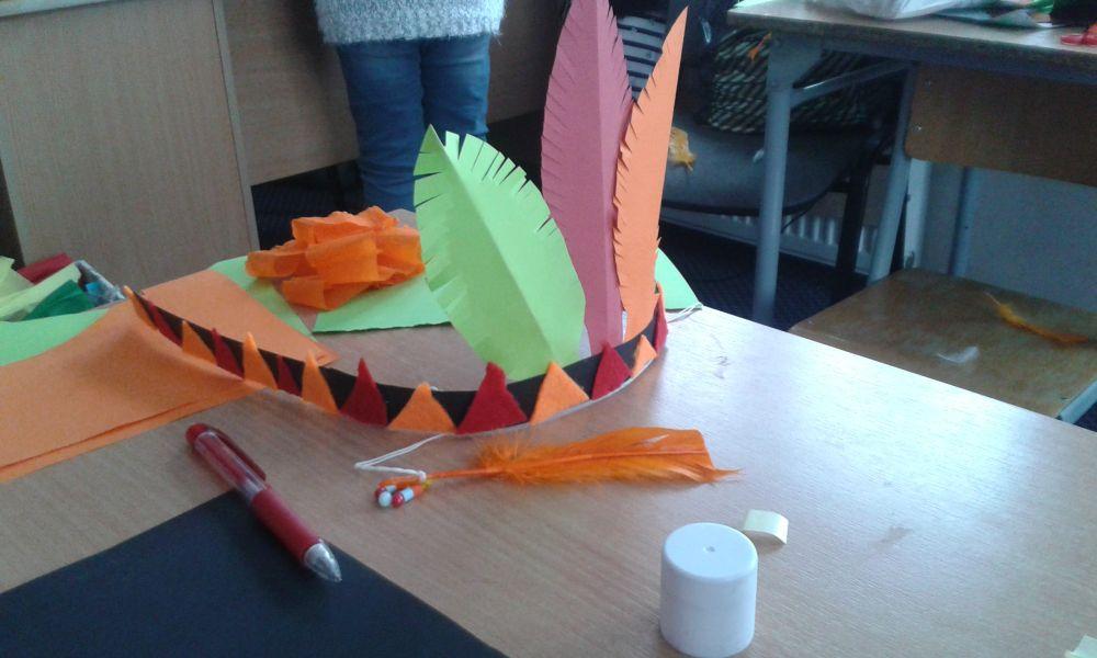 wykonany przez dziecko pióropusz indiański z przyklejonymi do opaski czerwonymi i pomarańczowymi trójkątami z filcu oraz wyciętymi z kolorowych kartek piórami