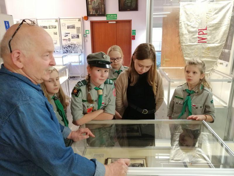 Harcerski w mundurach w Muzeum Harcerstwa oglądają zawartość jednej z gablot słuchając opowieści przewodnika