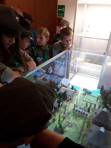 harcerze przyglądają się umieszczonej w gablocie makiecie obozu harcerskiego