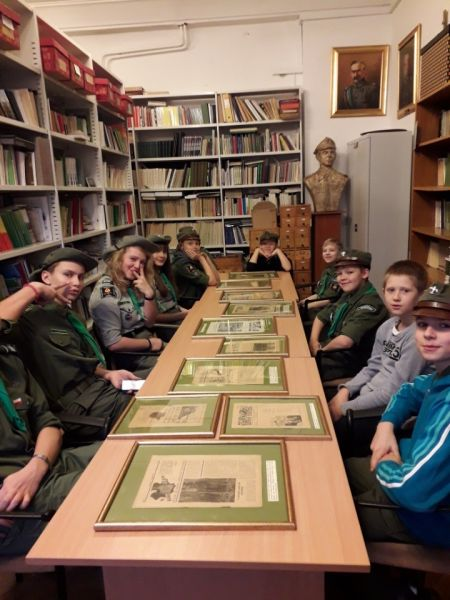 harcerze w bibliotece Muzeum Harcerstwa siedzą przy długim stole na którym rozłożone są w ramkach wydawane dawniej czasopisma o tematyce harcerskiej