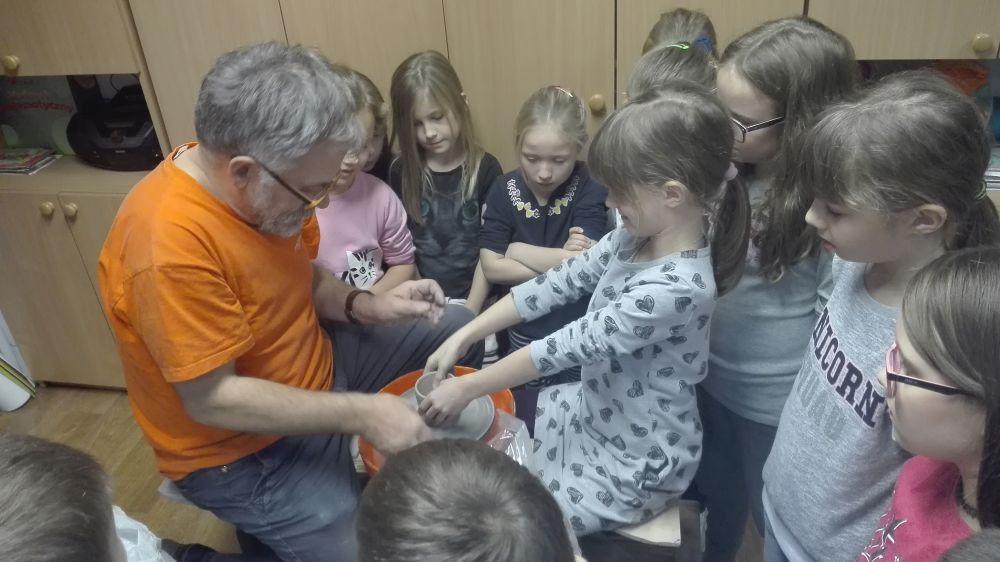 Dzieci słuchają opowieści Pana o właściwościach gliny