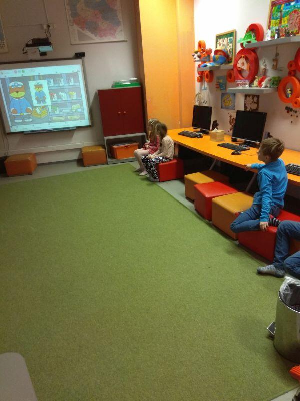 Dzieci oglądają wyświetlany materiał edukacyjny