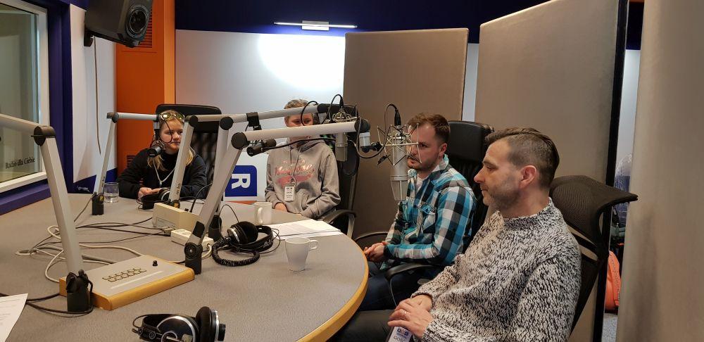 dyrektor szkoły, nauczyciel języka angielskiego i dwie uczennice siedzą w studio nagrań, przy mikrofonach