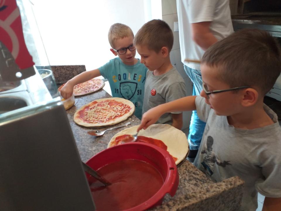 Chłopcy nakładają wybrane przez siebie składniki na ciasto