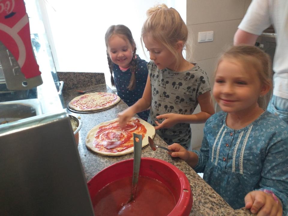 Dziewczynki nakładają wybrane przez siebie składniki na ciasto