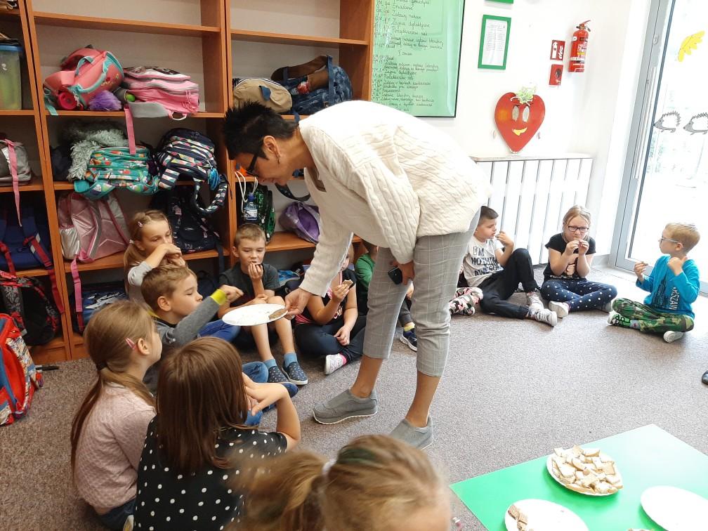 Wychowawca świetlicy częstuje dzieci chlebem
