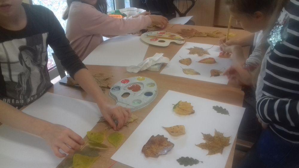 Dzieci wykonują pracę plastyczną z wykorzystaniem liści