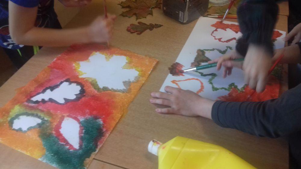 Dzieci malują tło wokół konturów liści farbami