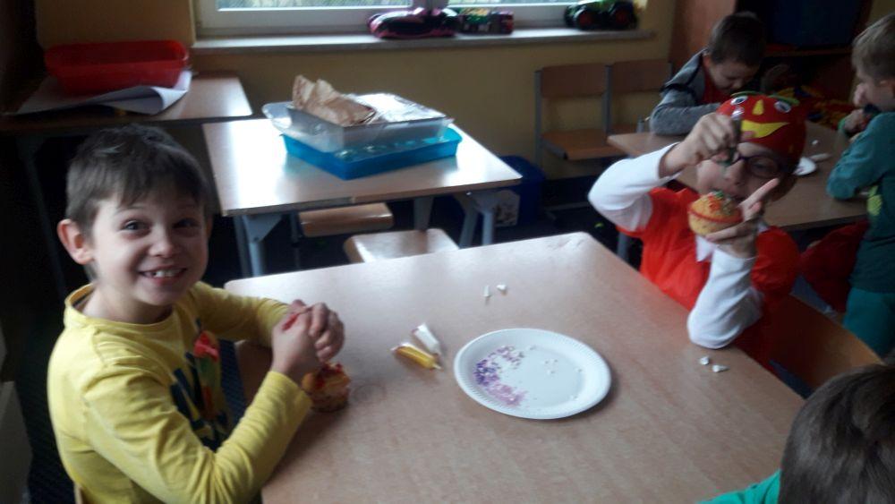 Uczniowie lasy I d ozdabiają babeczki cukrowymi pisakami