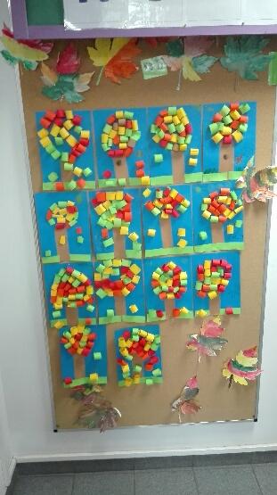 Prace wykonane przez dzieci z oddziałów przedszkolnych przedstawiające drzewa z pasków kolorowego papieru