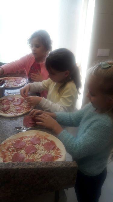 Uczennice klasy I d przyozdabiają pizze różnymi składnikami