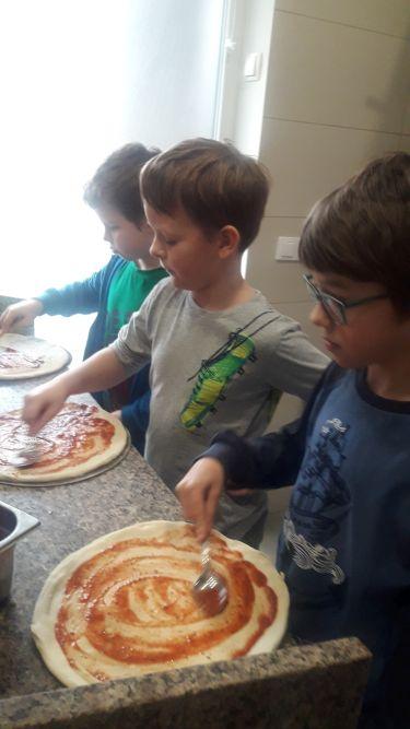 Chłopcy smarują blat pizzy sosem pomidorowym