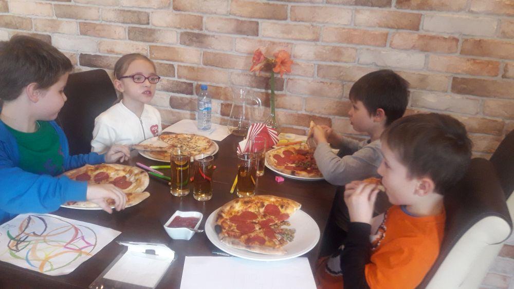 Dzieci jedzą pizzę