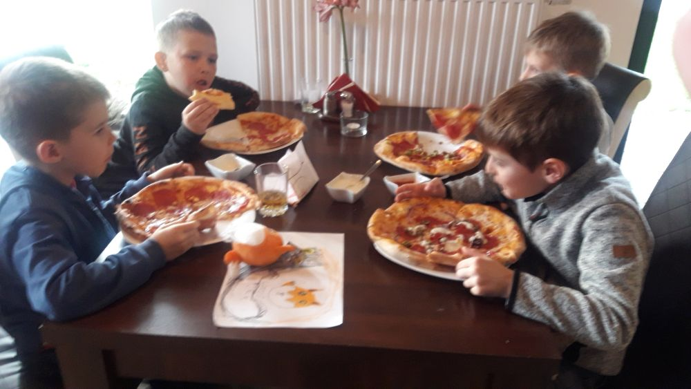 Uczniowie spożywają pizzę