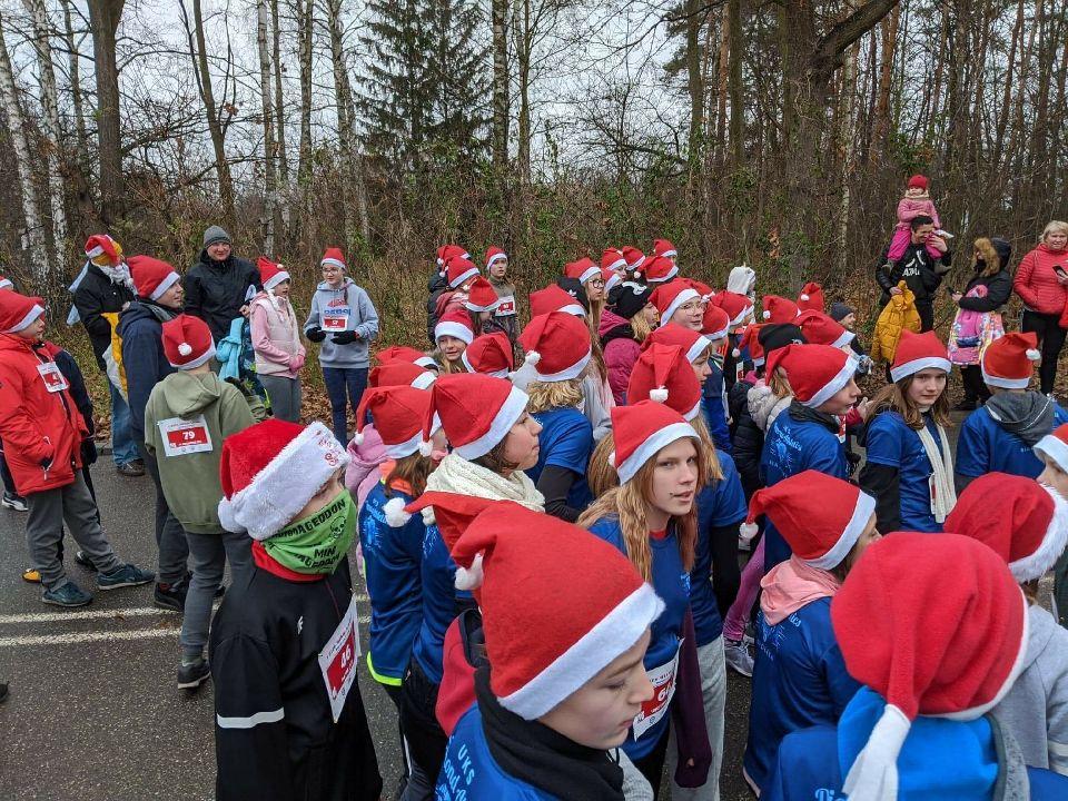 uczniowie w czapkach Mikołaja szykują się do biegu