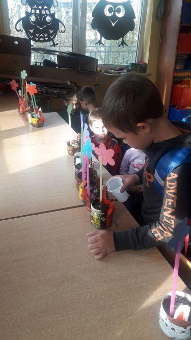 Uczeń klasy I d podlewa cebulki