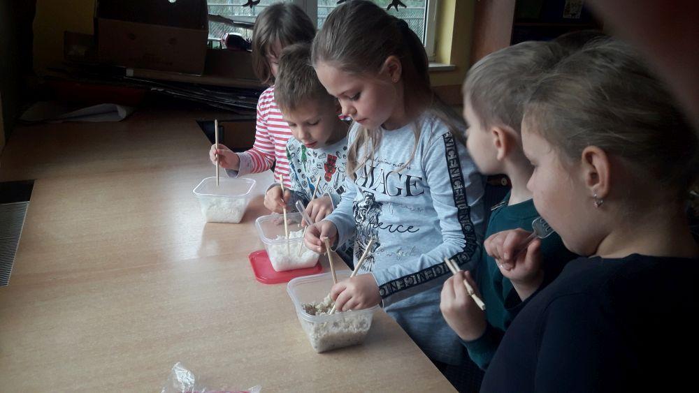 Dzieci próbują konsumować ryż pałeczkami
