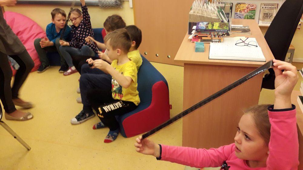 Dzieci podziwiają klisze, na których zapisane są bajkowe obrazy