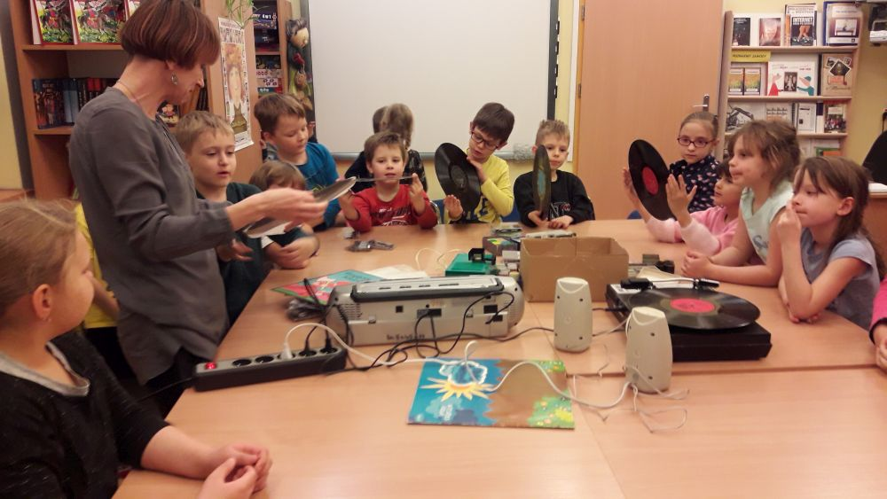 Dzieci dotykają i słuchają płyty na gramofonie